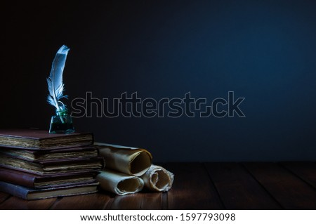 Quill pen and rolled papyrus sheets on a wooden table with old books Royalty-Free Stock Photo #1597793098