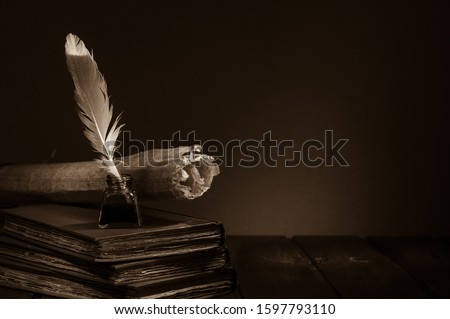 Quill pen and rolled papyrus sheets on a wooden table with old books, sepia effect Royalty-Free Stock Photo #1597793110