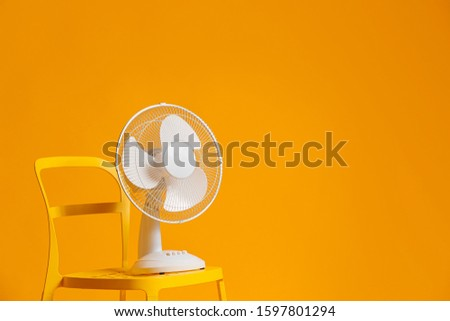 Electric fan on chair against color background #1597801294