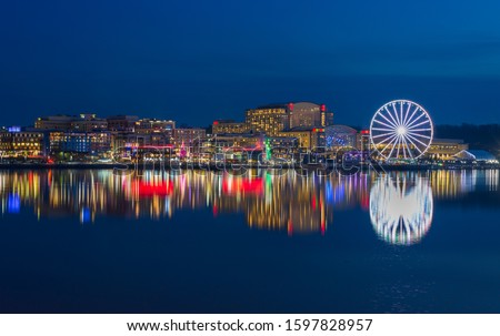Skyline of the National Harbor illuminated waterfront, a tourist attraction on the banks of the historic Potomac River in Prince Georges County Maryland. Royalty-Free Stock Photo #1597828957