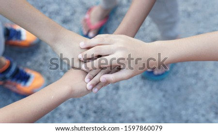 Hands of a kids puts together showing togetherness and unity. Friendship concept #1597860079