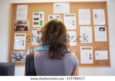 Student studying notice board in school Royalty-Free Stock Photo #159788417