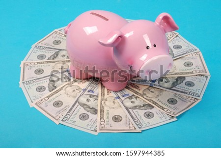 Pink piggy bank on money, in the shape of a circle isolated on blue background. Abstract money background raster pattern repeat circle.  High resolution photo.