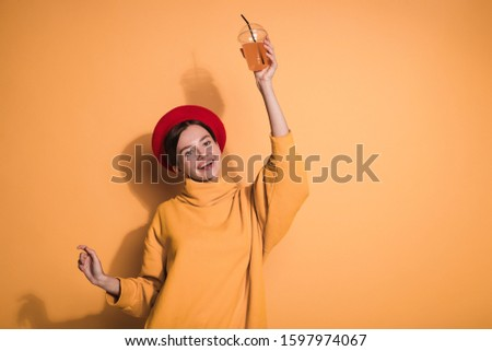Cheerful playful young woman posing on camera alone. Hold drink in one hand. Look straight and smile. Wear red beret and stylish sweater. Isolated over yellow background #1597974067