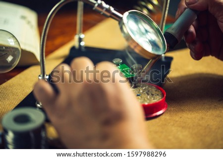 Hands of man holding solder iron  soldering the pin on electronics circuit board,  DIY hobbies and electrician workshop concept. #1597988296