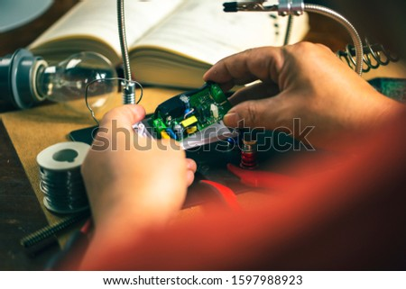 Hands of man holding solder iron  soldering the pin on electronics circuit board,  DIY hobbies and electrician workshop concept. #1597988923