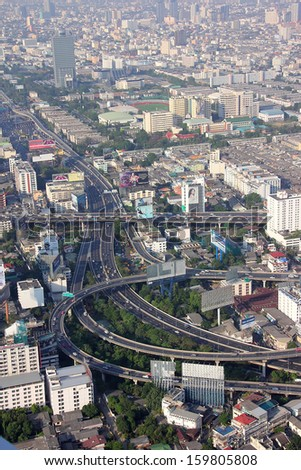 BANGKOK, THAILAND - MARCH 19, 2013: Some of Bangkok's famous expressways seen from above. In the Background are the towers and skyscrapers of the city. #159805808