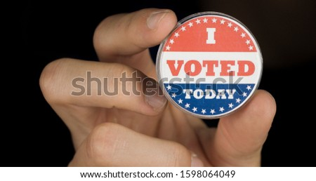 Closeup shot of a hand holding I voted today button. American elections concept #1598064049