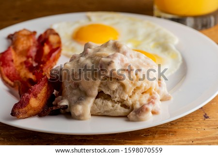 Bacon, Eggs and biscuits. Traditional classical American diner or French Bistro brunch item favorite. Biscuits and White Gravy. Homemade white sausage gravy served with fried eggs and crispy bacon.  #1598070559
