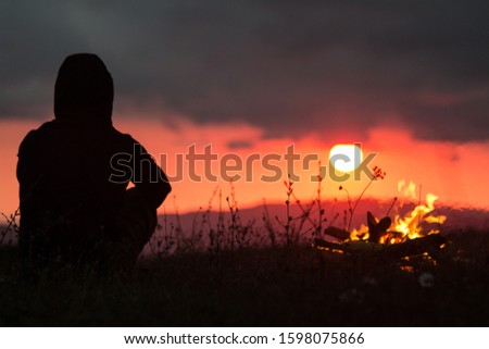 Silhouette of a man near a fire on a background of sunrise #1598075866