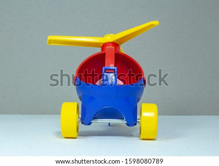 Children's toy, plastic red-blue helicopter with a yellow propeller and wheels on a gray fleecy background