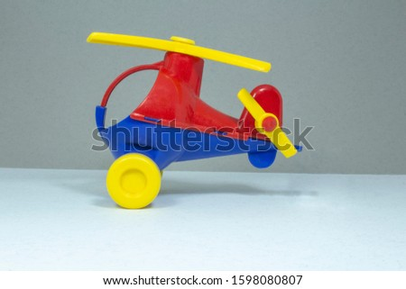 Children's toy, plastic red and blue helicopter with a yellow propeller and wheels on a gray fleecy won