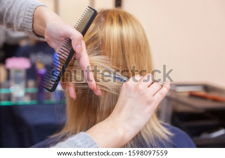 The hairdresser does a haircut with scissors of hair to a young girl, a blonde in a beauty salon.  Professional hair care. #1598097559