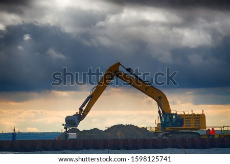 Excavator performs land work on the sea berth. Construction of the pier. Construction in the precess of the Nord stream 2 gas pipeline #1598125741