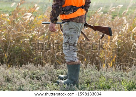 A man with a gun in his hands and an orange vest on a pheasant hunt in a wooded area in cloudy weather. Hunter in search of game. #1598133004