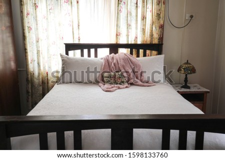 Floral embroidered pillow and pink blanket on queen size bed in country cottage bedroom  #1598133760