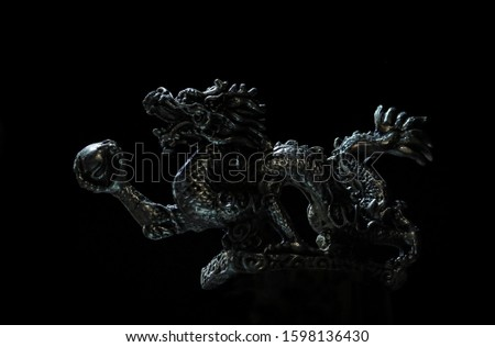 Close up. The design of a Dragon is made of bronze with a dark background #1598136430