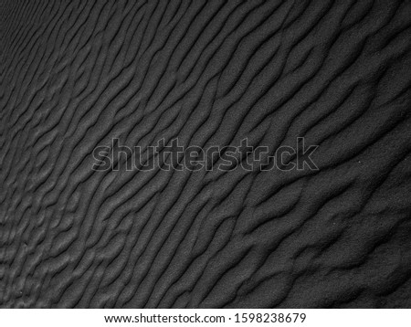 Black Sand beach macro photography. Texture of black volcanic sand for background. Close-up macro view of volcanic sand surface black color. Black and white poster texture sand in the desert.  #1598238679
