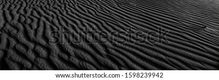 Black and white poster texture sand in the desert. Panaroma Sand texture. abstract texture line wave. Sand Waves Abstract Black and White background. Volcanic rock texture. Black salt. Black Sand. Royalty-Free Stock Photo #1598239942