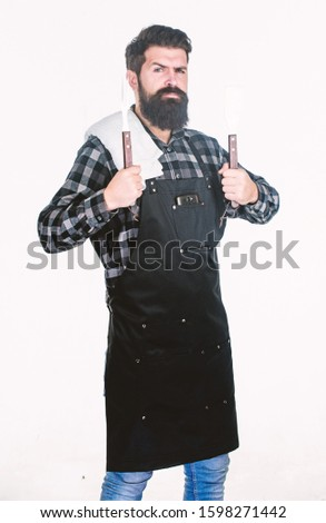 Bearded hipster wear apron for barbecue. Roasting and grilling food. Man hold cooking utensils barbecue. Tools for roasting meat outdoors. Picnic and barbecue. Cooking meat in park. Barbecue master. #1598271442