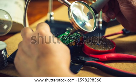Hands of man holding solder iron  soldering the pin on electronics circuit board,  DIY hobbies and electrician workshop concept. #1598298568