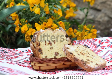 Painted Easter eggs, slices of Easter cake on an embroidered napkin - traditional Easter breakfast, decorated in rustic style, selective focus