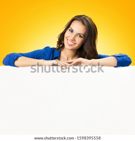 Portrait of happy smiling young woman holding blank sign board with copy space, isolated over yellow orange  background. Success in business concept. Brunette model in blue clothing at studio picture.