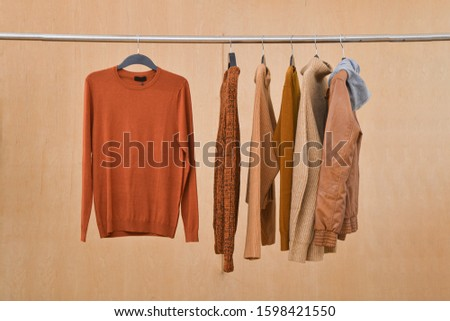 brow knitwear ,sweater and brown jacket are hanging on Clothes Hanger,-wooden background  #1598421550