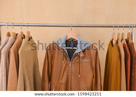 brow knitwear ,sweater and brown jacket are hanging on Clothes Hanger,-wooden background  #1598423251