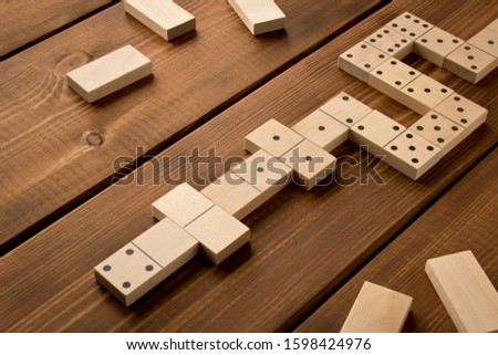 Playing dominoes on a wooden table. Leisure games concept. Selective focus #1598424976