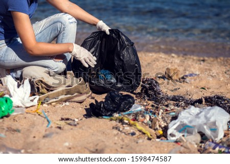 Woman volunteer with black bag collect garbage on the beach. Environmental pollution concept #1598474587