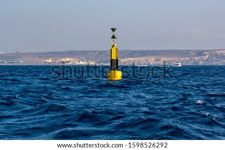 Yellow and black steel navigational floating buoy - West cardinal mark - in the blue Mediterranean sea water between Comino and Malta islands. Royalty-Free Stock Photo #1598526292