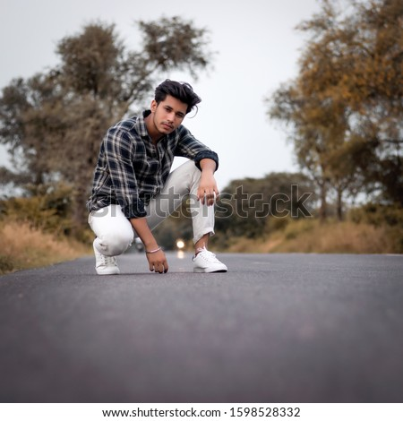 Young Indian boy sitting on the road posing for the camera  Royalty-Free Stock Photo #1598528332