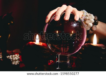 Fortuneteller's hand on a glass orb. Prediction of the future. Mystic interior. Occult symbols #1598550277