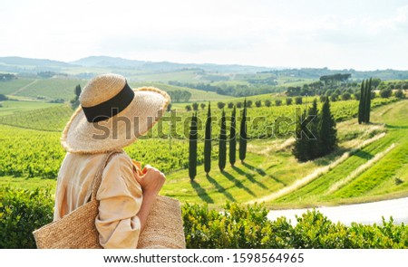 A girl in a straw hat, a linen shirt with a wicker bag on the background of the Tuscan landscape. Italian vacation.