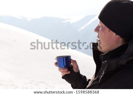 Young smiling man photographer in winter clothing drinking tea from thermos and smiling in sunlight with white snow background. Travelling and making photos of winter nature concept #1598588368