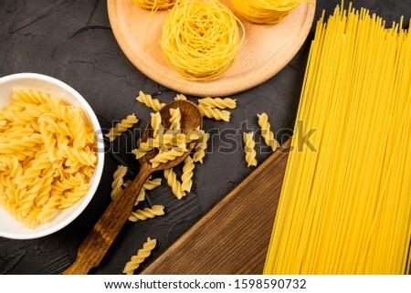 uncooked pasta variations on white wood table #1598590732