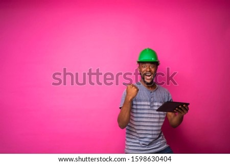 Young handsome black engineer wearing a green hard hat, working on his tablet to fix some engineering work online #1598630404
