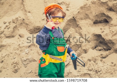 Happy master. Future profession. Carnival for children in the kindergarten. A boy in a suit of a builder. Tools for mens work. Repair and construction. #1598719708