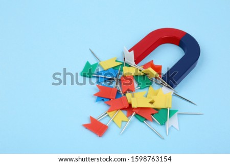 Magnet attracting colorful pins on light blue background #1598763154