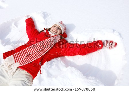 Beautiful joyful young woman laying down on a frozen snow lake moving her arms up and down creating an angel figure shape, playing games while on vacation during a sunny winter day.