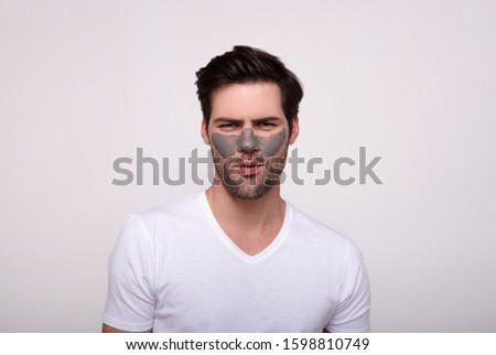 A handsome handsome, handsome Caucasian man with a beard, wearing a white T-shirt, wearing face mask stands up straight and looks into the camera posing against a white background. Skin care concept. #1598810749