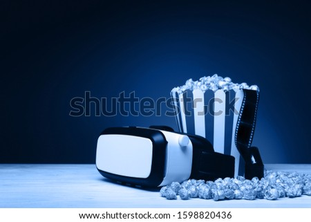 Composition with cinema film, a bucket of popcorn and VR headset on the wooden table. Toned in trendy classic blue color year 2020 #1598820436