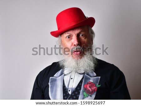 Happy old man in a fake tuxedo wearing a red bowler hat and making facial expressions. Old Caucasian with a long white beard, faux tuxedo and red bowler hat making  faces and an outrageous expression. #1598925697