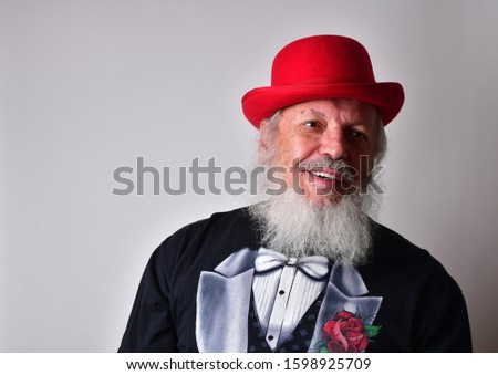 Happy old man in a fake tuxedo wearing a red bowler hat and making facial expressions. Old Caucasian with a long white beard, faux tuxedo and red bowler hat making  faces. #1598925709