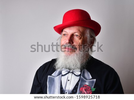 Happy old man in a fake tuxedo wearing a red bowler hat and making facial expressions. Old Caucasian with a long white beard, faux tuxedo and red bowler hat making  faces. #1598925718