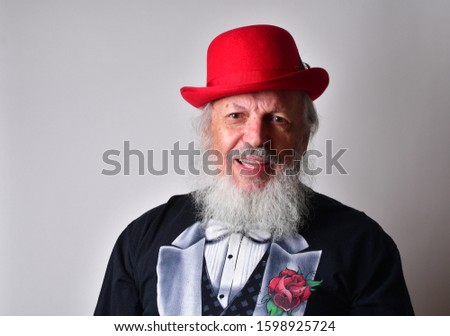 Happy old man in a fake tuxedo wearing a red bowler hat and making facial expressions. Old Caucasian with a long white beard, faux tuxedo and red bowler hat making  faces. #1598925724