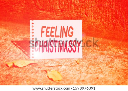 Handwriting text Feeling Christmassy. Concept meaning Resembling or having feelings of Christmas festivity Empty Spiral Bound Notebook Sheet Torn Off Folded in Half Dried Leaves. #1598976091