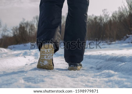 A man walks alone in the park in winter after a snowfall. Walking concept. Rear view of a pedestrian. #1598979871