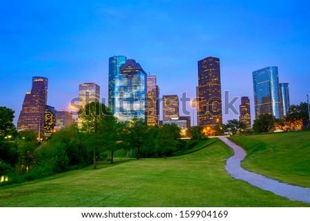 Houston Texas modern skyline at sunset twilight from park lawn